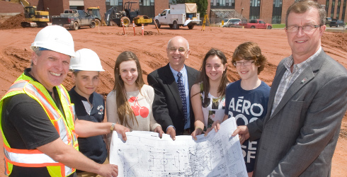 Students look over plans for the Souris K-12 school with building design and construction manager Tyler Richardson (left), English language school board chair Fred Osborne (center) and P.E.I.Education and Early Childhood Development Minister Alan MacIsaac.